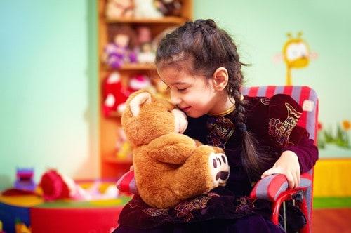 girl in wheelchair hugging toy - teach kids meditation