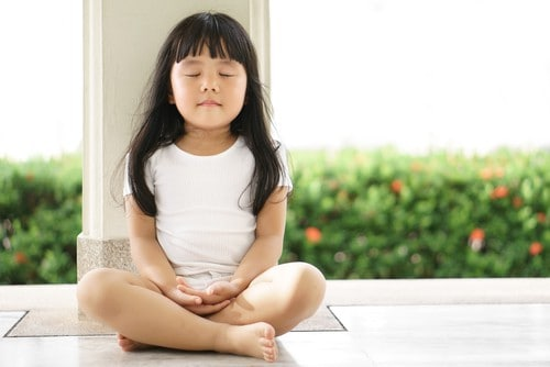 small girl meditating - teach kids mindfulness